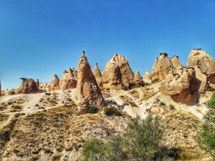 Rock formations in desert against clear blue sky