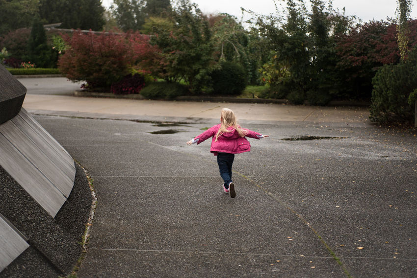 A young girl runs in a park on a cloudy wet day. Away Blond Hair Casual Clothing Childhood Cute Day Fall Family Full Length Girls Happy Kid Leisure Activity Lifestyles Motion Nature One Person Outdoors Park People Play Real People Run Runner Young