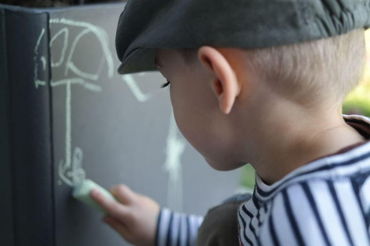 Boy drawing with chalk in classroom