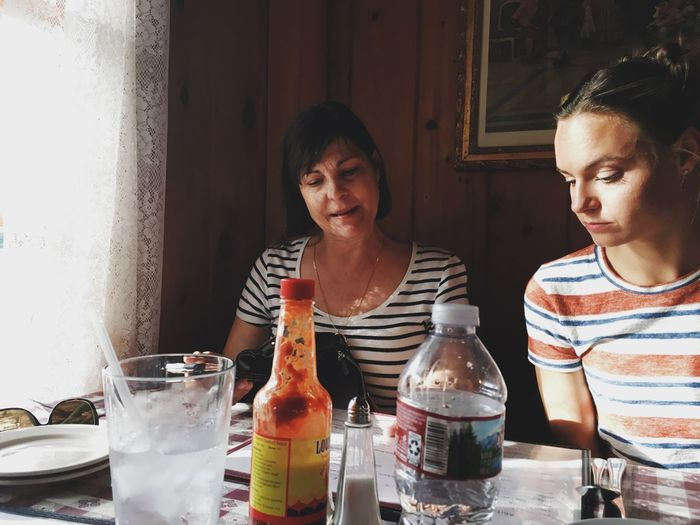 Mother and daughter sitting at table in restaurant