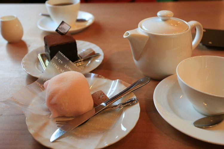 Close-Up Of Tea Cup With Cake Slice On Table