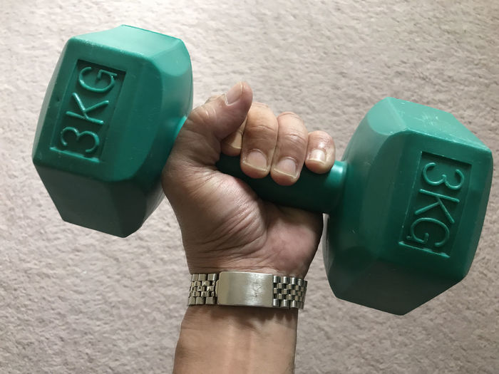 Cropped Hand Of Man Lifting Dumbbell Against Wall