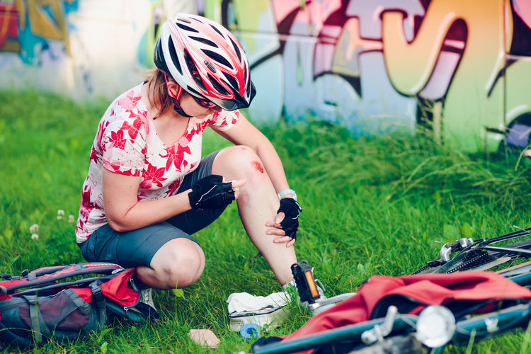 Injured Female Cyclist Looking At Wound While Crouching At Park
