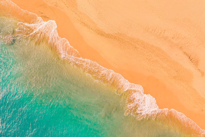 Aerial view of atlantic ocean coast with crystal clear turquoise water, waves rolling into the shore