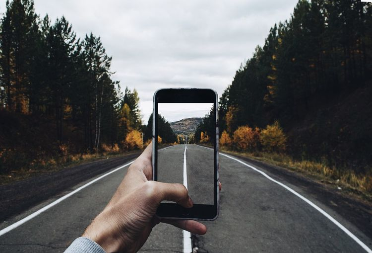 Human Hand Human Body Part Road Personal Perspective Tree Holding Transportation Real People Sky One Person Day Outdoors Mobile Phone Nature Land Vehicle Landscape Wireless Technology Photography Themes Close-up A New Perspective On Life