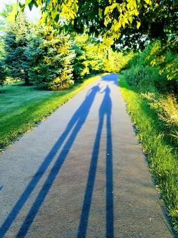 Shadow Real People Focus On Shadow Long Shadow - Shadow Sunlight Day Togetherness Two People Outdoors Men Green Color Tree Love Leisure Activity Nature Growth Road Lifestyles Bonding Grass