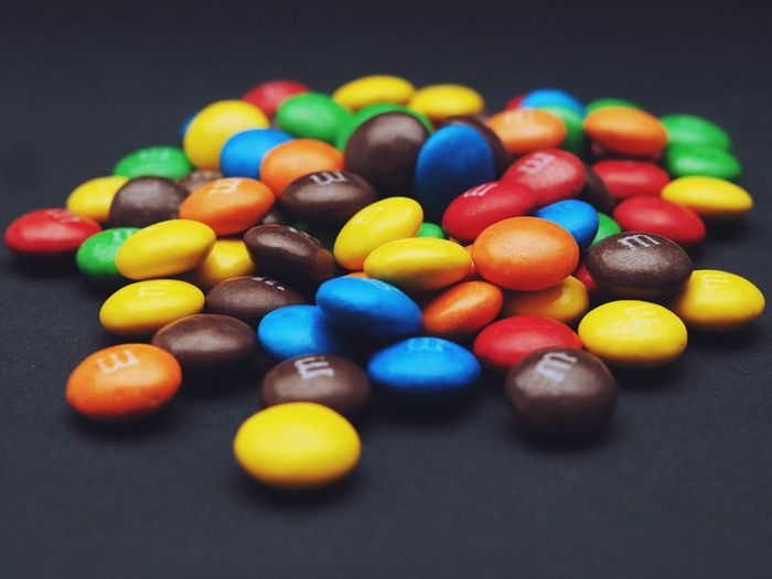 Close-up of colorful candies on table against black background