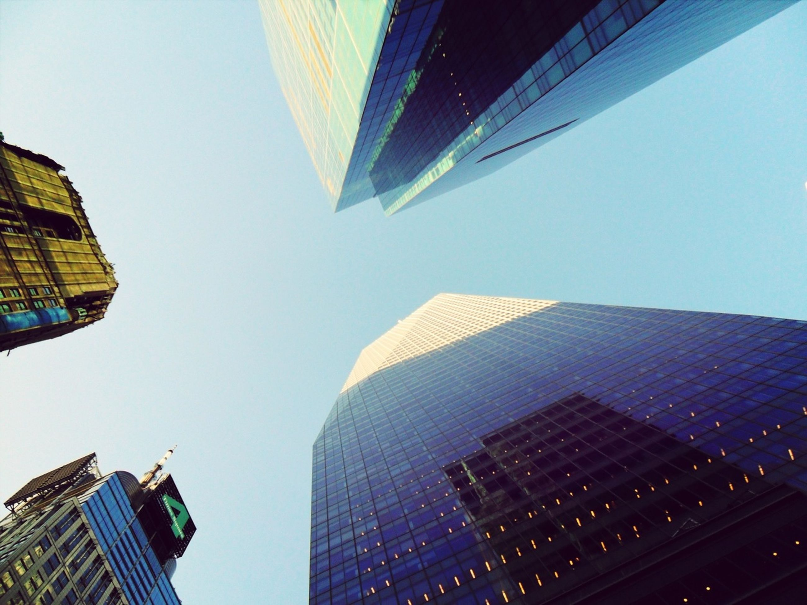 building exterior, architecture, built structure, skyscraper, modern, city, low angle view, office building, tall - high, tower, clear sky, building, city life, glass - material, financial district, blue, development, tall, reflection, day