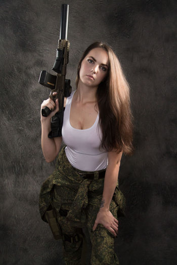 Adult Aggression  Beautiful Woman Beauty Gun Hair Hairstyle Handgun Holding Long Hair Looking At Camera One Person Portrait Standing Studio Shot Three Quarter Length Weapon Young Adult Young Women