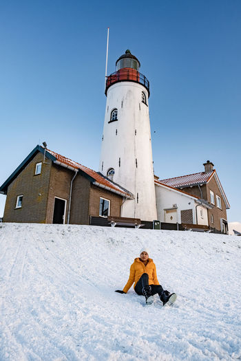 Full length of couple sitting on snow covered land against lighthouse