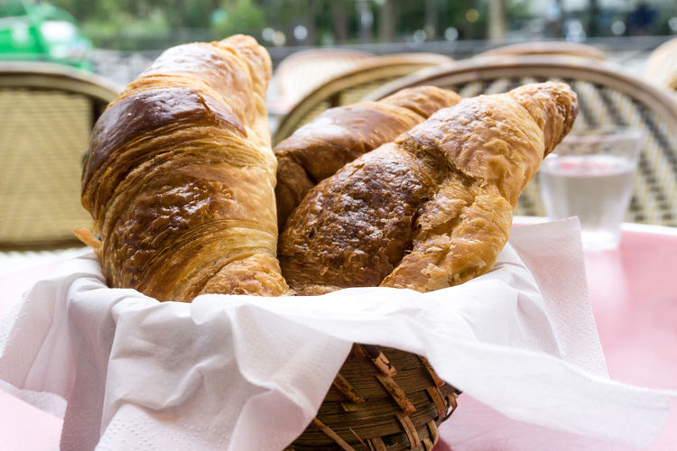Close-up of croissants in wax paper at table