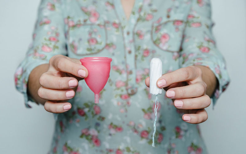 Midsection of woman holding cup and tampon