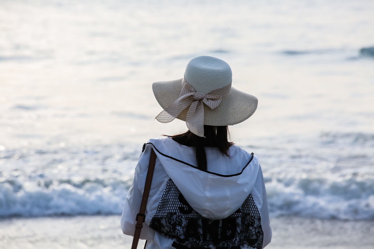 hat, rear view, real people, beach, one person, outdoors, lifestyles, focus on foreground, women, sea, standing, leisure activity, day, sunlight, water, nature, sun hat, sand, beauty in nature, people