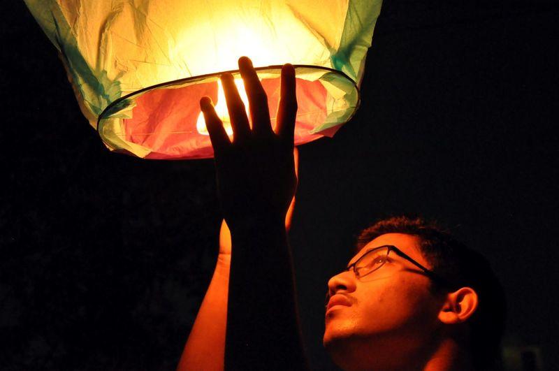 Close-up of teenage boy releasing lit paper lantern at night