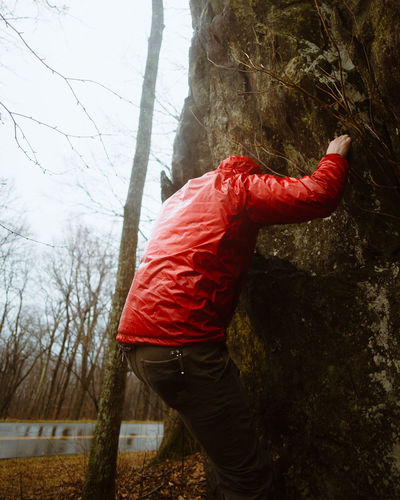 Side view of man standing by tree trunk
