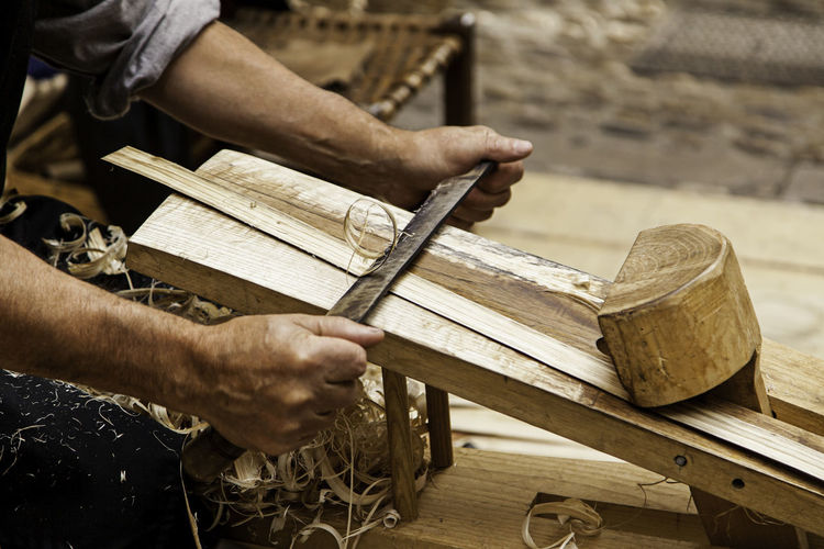 Midsection of man carving wood at workshop