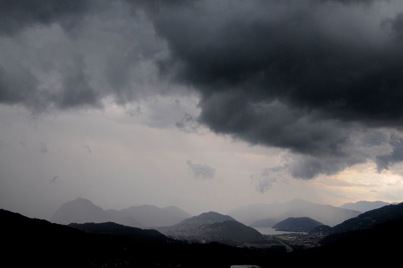 Scenic view of dramatic sky over silhouette mountains