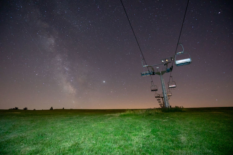 Low angle view of chair lift on field against sky