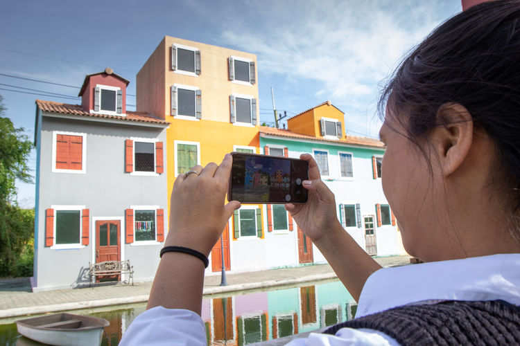 Rear view of woman photographing building