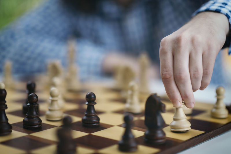 Playing chess. hand of a male chess player moving the white chess piece.