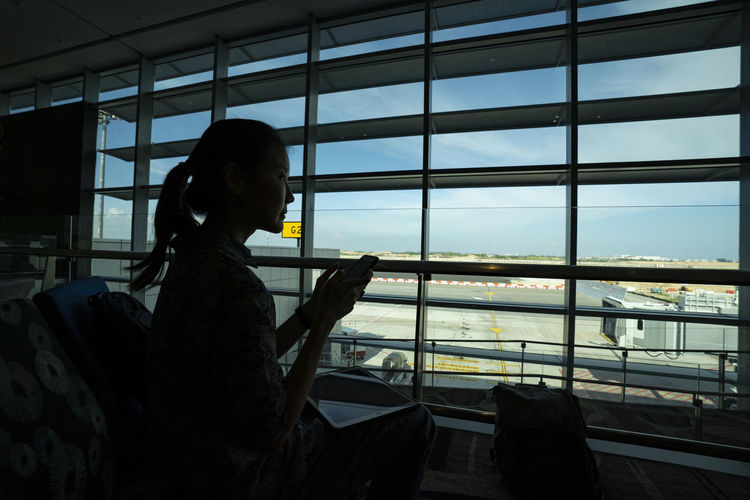 Side view of woman looking through window at airport