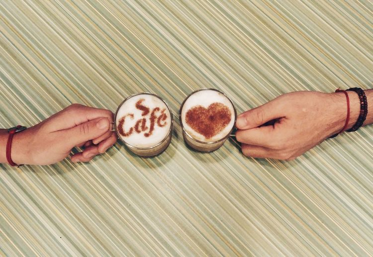 High Angle View Of Hands Holding Coffee Cups On Table