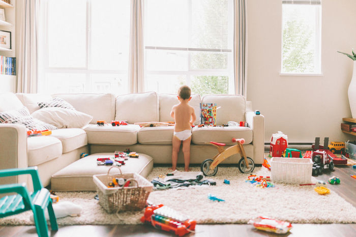 Rear view of boy playing with toys in living room at home