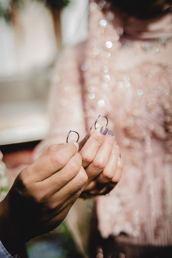 Midsection of bride and groom holding rings