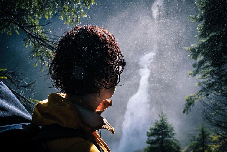 Close-up of man looking at waterfall