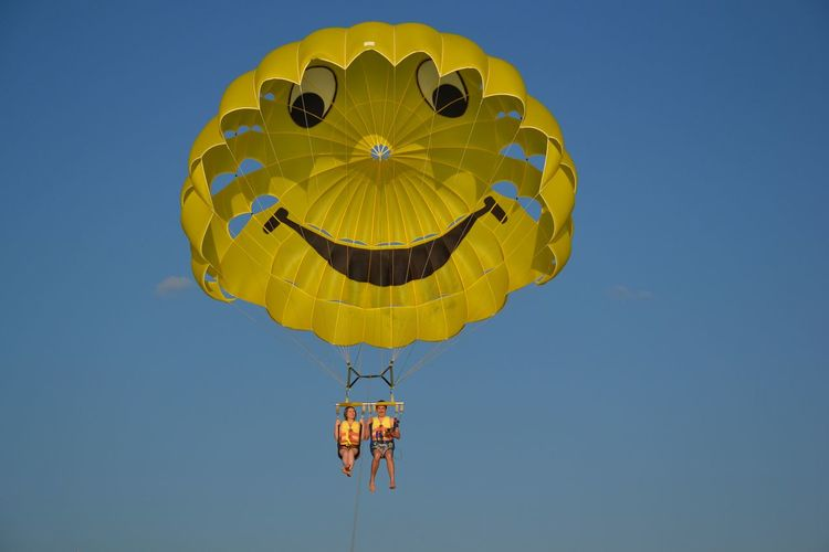 Full length portrait of smiling couple parasailing against sky
