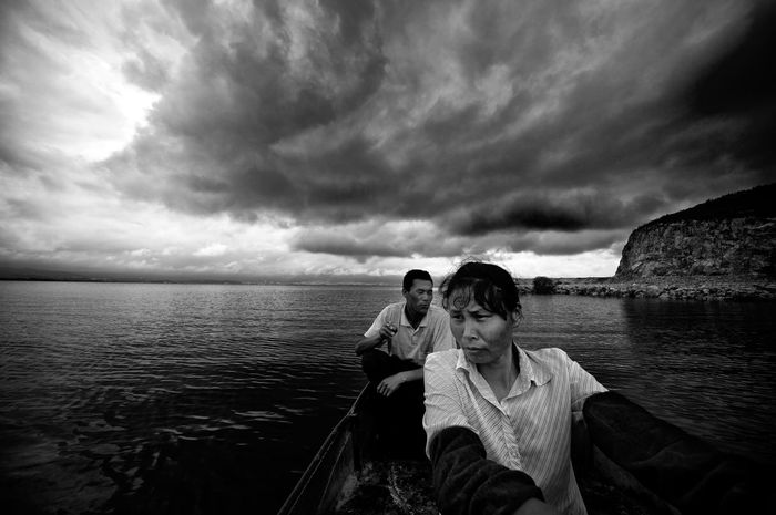 Fishermen of Erhai Lake Husband and wife brave the incoming storm on their tiny boat to make their livelihood fishing on Erhai Lake, Yunnan, China. On the distance you can barely distinguish the skyline of Dali. Black & White Braving The Storm Braving The Elements Erhai Lake,Dali Weather Working Working Hard Blackandwhite China Cloud - Sky Couple - Relationship Fishermen Fishing Hard Life Horizon Over Water Lake Mature Couple Nature Outdoors People At Work Real People Reportage Water