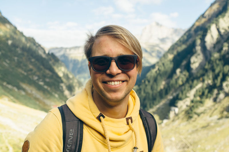 Portrait of smiling young man in mountain valley