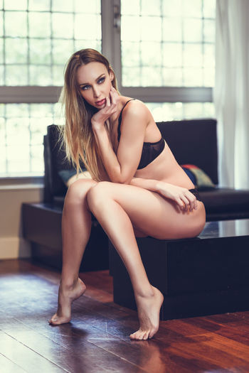 Sensuous Woman Sitting On Table Against Window At Home