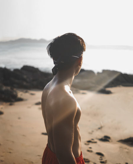Rear view of shirtless man standing on beach