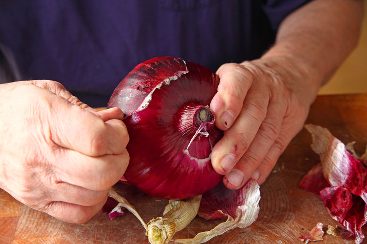 A man peeling the rough outer skin of a large red onion Copy Space Hands Man Natural Light Arm Black Tshirt Casual Clothing Close-up Cutting Board Day Dirty Hands Fingers Food Food Preparation Holding One Man Only One Person Peeling Red Onion Room For Text Root Vegetable Studio Shot Vegetable