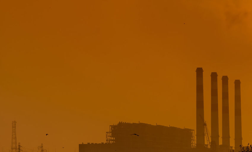 Power plant with orange sunset sky and birds flying on the sky. air pollution concept.