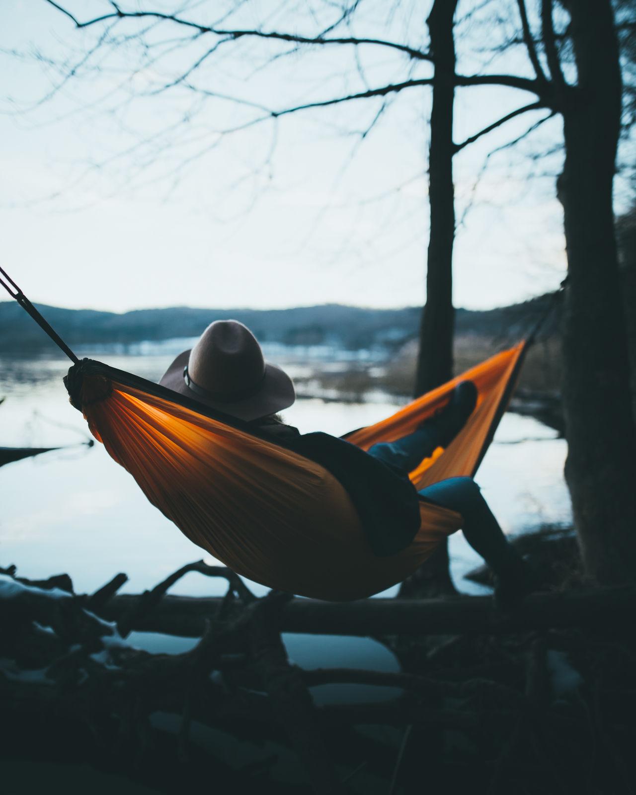 Man sitting on hammock against sky