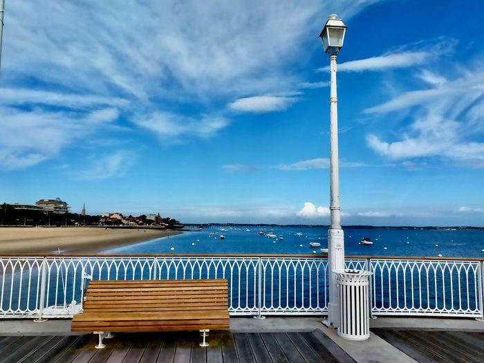Pier by sea against blue sky
