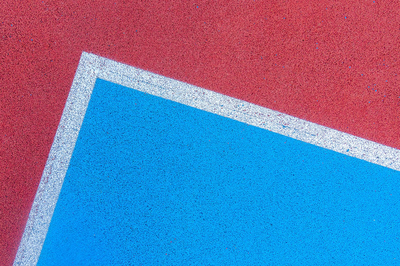 Colorful sports court background. top view to red and blue field rubber ground with white and lines