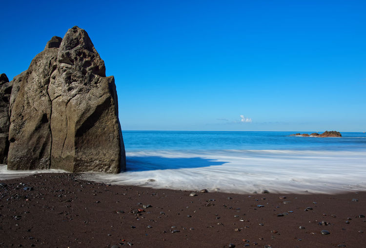 Rock formation on Praia Formosa beach on Madeira island Black Sand Beach Motion Long Exposure Madeira No People Rock Formation Clear Sky Solid Rock - Object Nature Tranquil Scene Tranquility Blue Rock Horizon Horizon Over Water Beauty In Nature Scenics - Nature Beach Sky Water Sea Praia Formosa Beach - Madeira