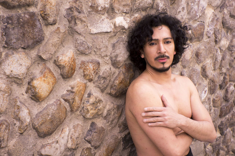 Portrait Of Shirtless Mature Man Standing Against Wall