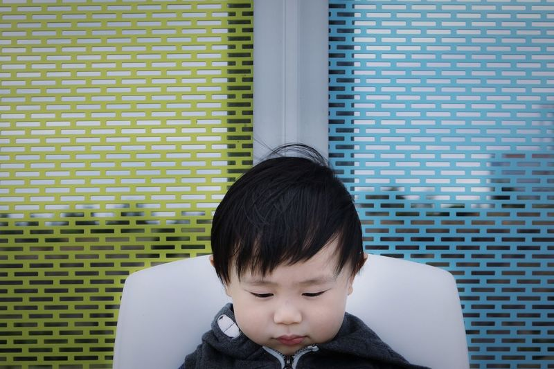 Close-up of cute boy against window