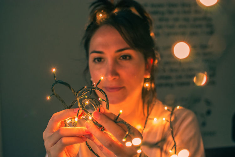 Woman Holding Illuminated String Lights While Sitting In Darkroom