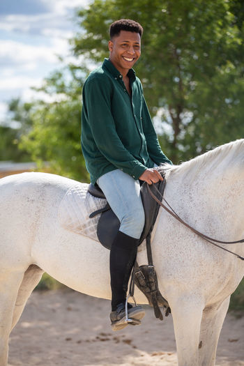 Portrait of smiling man riding horse