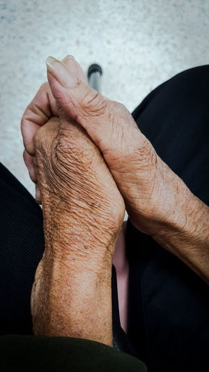 Midsection of senior woman with hands clasped