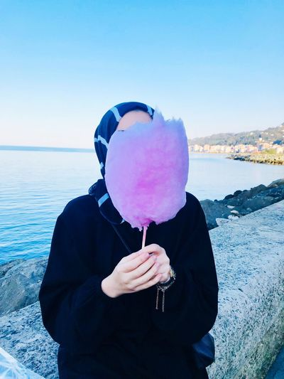 Woman covering face with purple cotton candy against sea
