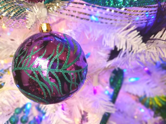 Purple and green striped ornament on a white Christmas tree Purple White Christmas Tree Disco Ball Christmas Tree Close-up Celebration Event Shiny Holiday - Event Indoors