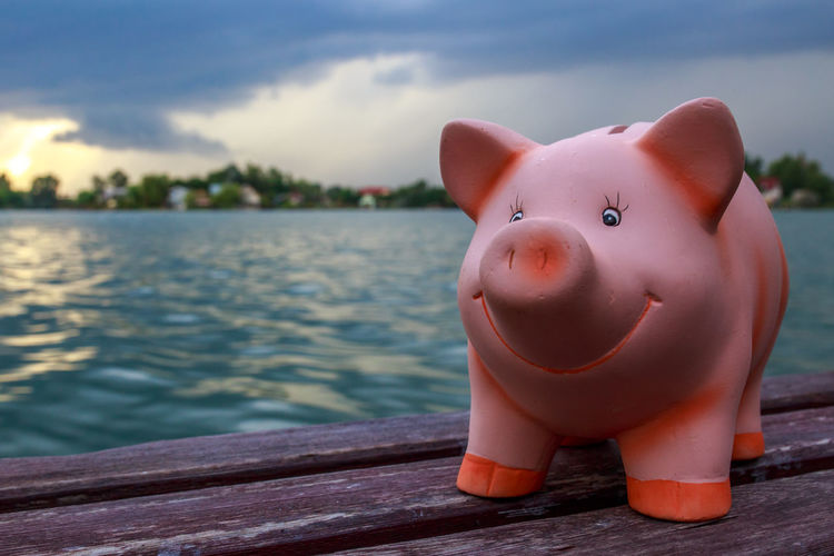 Close-up of piggy bank on table at lake against sky