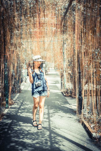 Woman walking on walkway amidst dry vines