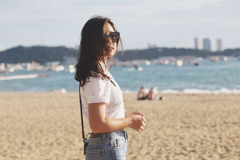 Young woman standing on beach against sea
